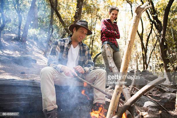 Young male and female hikers tending campfire in forest, Arcadia, California, USA