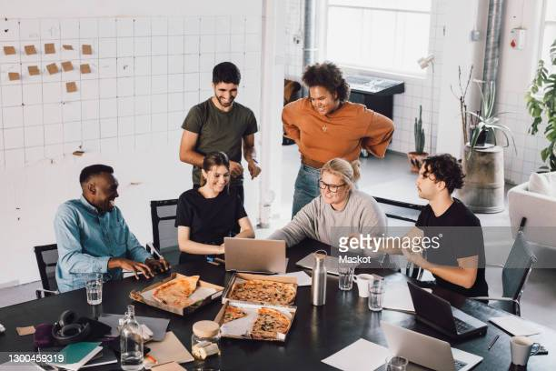 young male and female it professionals in meeting while eating pizza at office - coinvolgimento dei dipendenti foto e immagini stock
