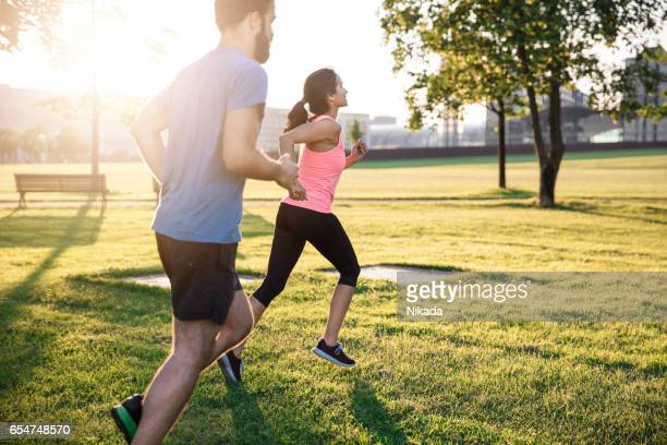 Young male and female jogging in city at sunset