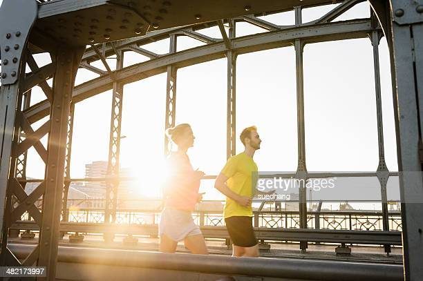 Young male and female running across bridge