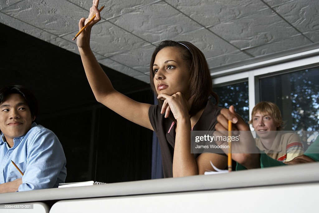 Young male and female students in auditorium, one raising hand : Stock Photo