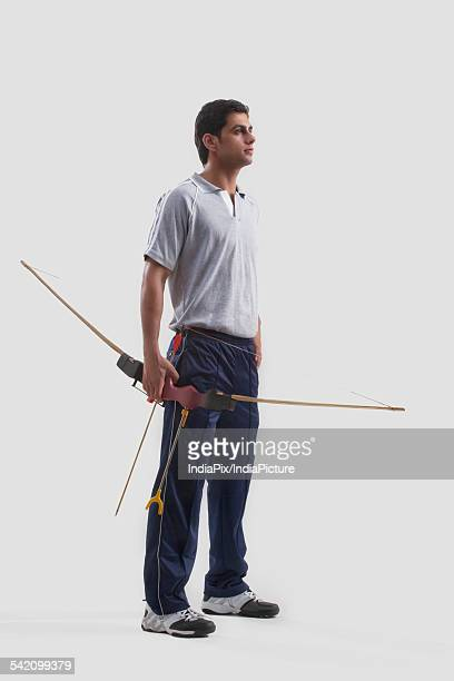 Young male archer standing with bow and arrow isolated over gray background