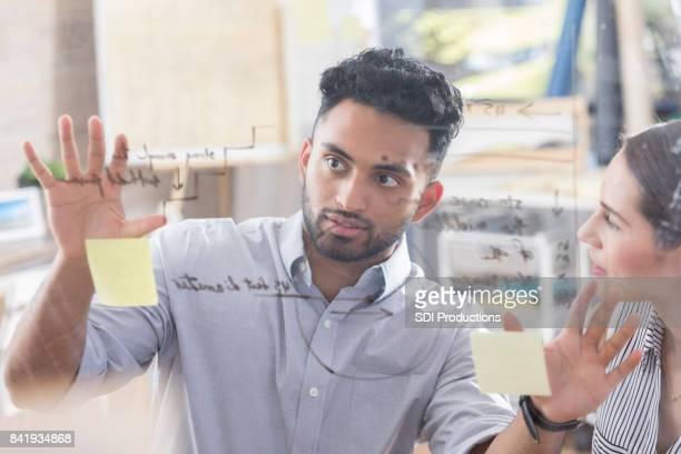 Joven arquitecto hombre explica ideas a compañero de trabajo