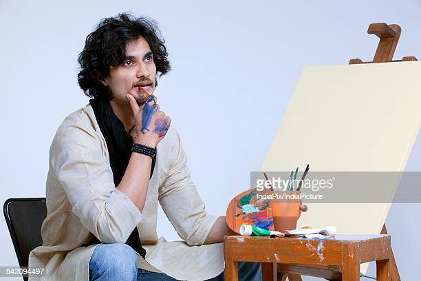 Young male artist contemplating near easel against colored background