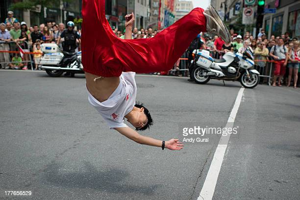 Young male asian performs a leap during a parade. He is airborne and upside down. Police motorcycles, spectators and an urban environment are visible...