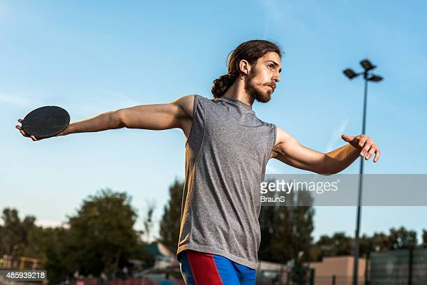 Young male athlete about to throw a discus.