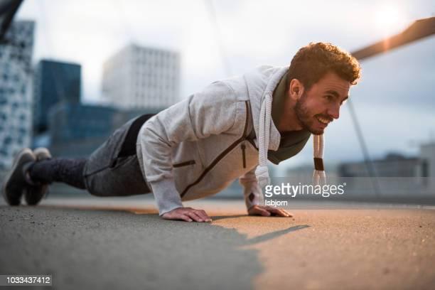 Junge Sportler tun Push Ups im Zentrum der Stadt bei Sonnenuntergang.