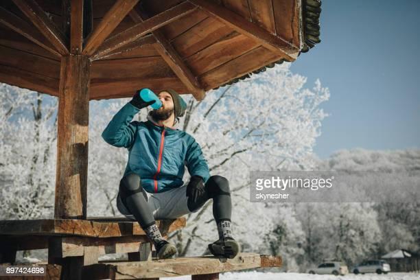 Junge männliche Athlet Trinkwasser bei einer Pause im Wintertag.