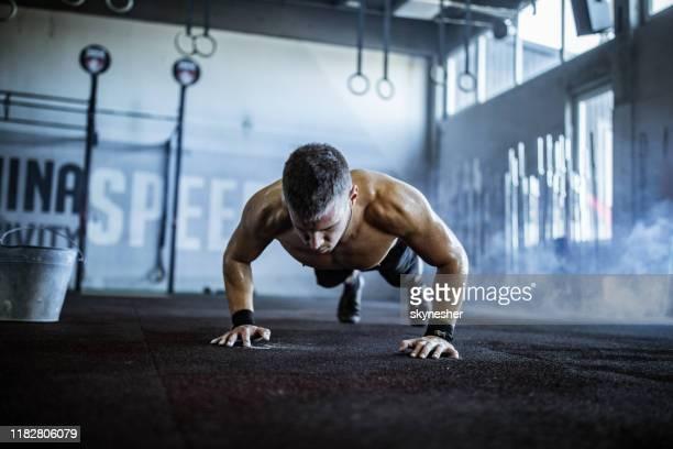 ヘルスクラブで腕立て伏せをする若い男性アスリート。 - 練習 ストックフォトと画像