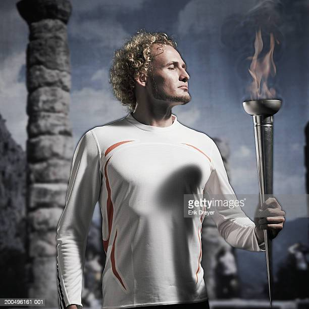 young male athlete holding olympic torch - 聖火トーチ ストックフォトと画像