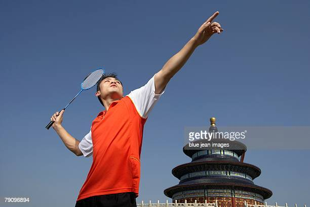 a young male athlete holds his badminton racquet at the ready, beijing's temple of heaven behind. - スポーツ バドミントン ストックフォトと画像
