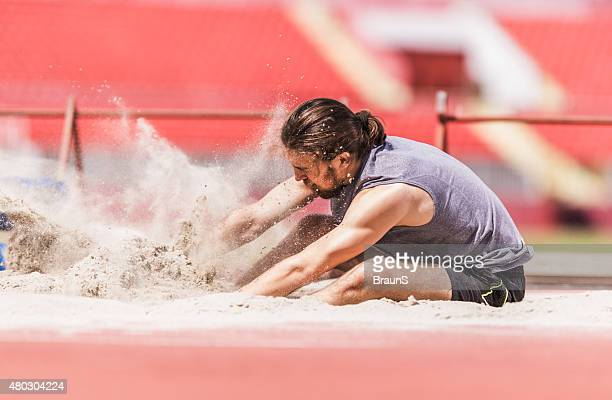 Young male athlete landing in sand after a long jump.