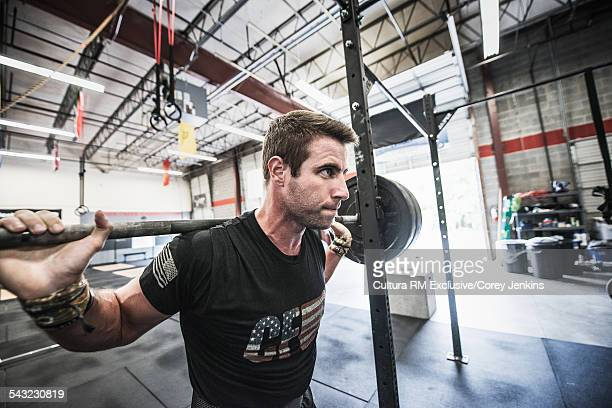 Young male athlete lifting bar bell on shoulders in gym