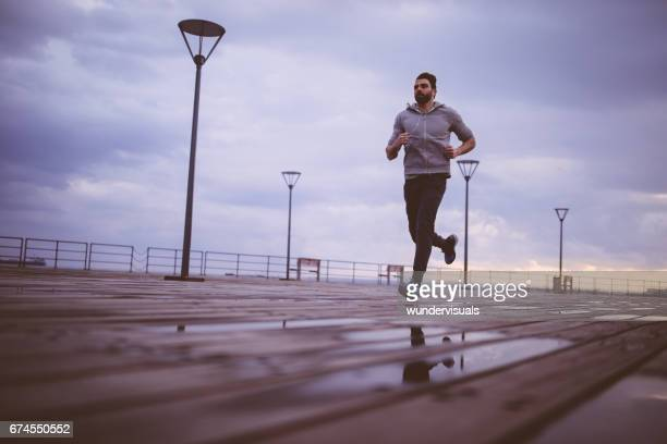 young male athlete running on a wooden jetty at sunrise - sport venue stock pictures, royalty-free photos & images