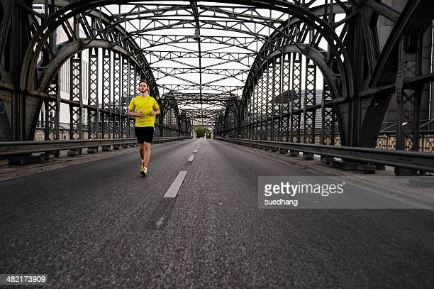Young male athlete running on bridge
