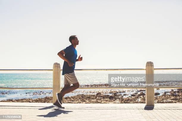 young male athlete running on promenade at beach - caratteristica costiera foto e immagini stock