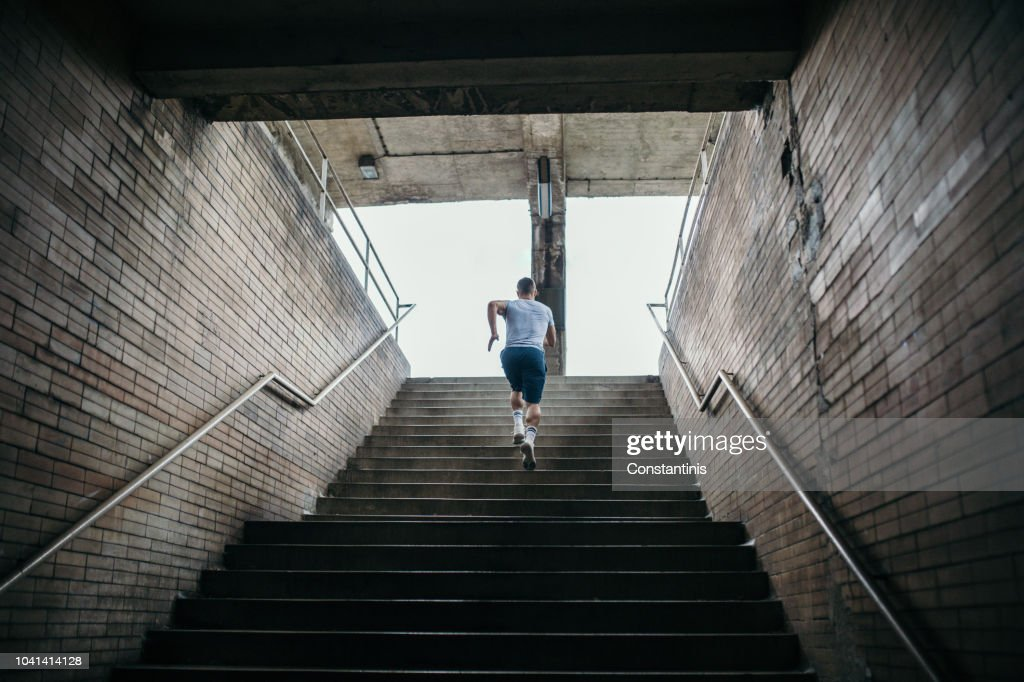 Young male athlete running up the stairs : Stock Photo