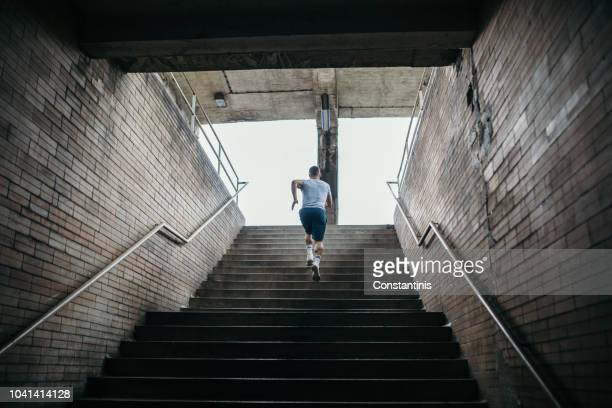 young male athlete running up the stairs - steps stock photos and pictures
