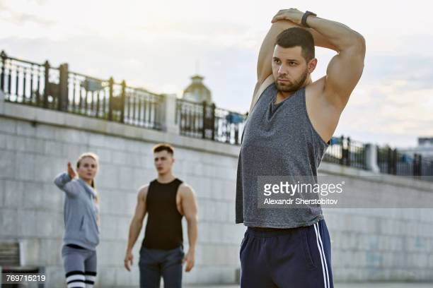 Young male athlete stretching with friends in background against bridge