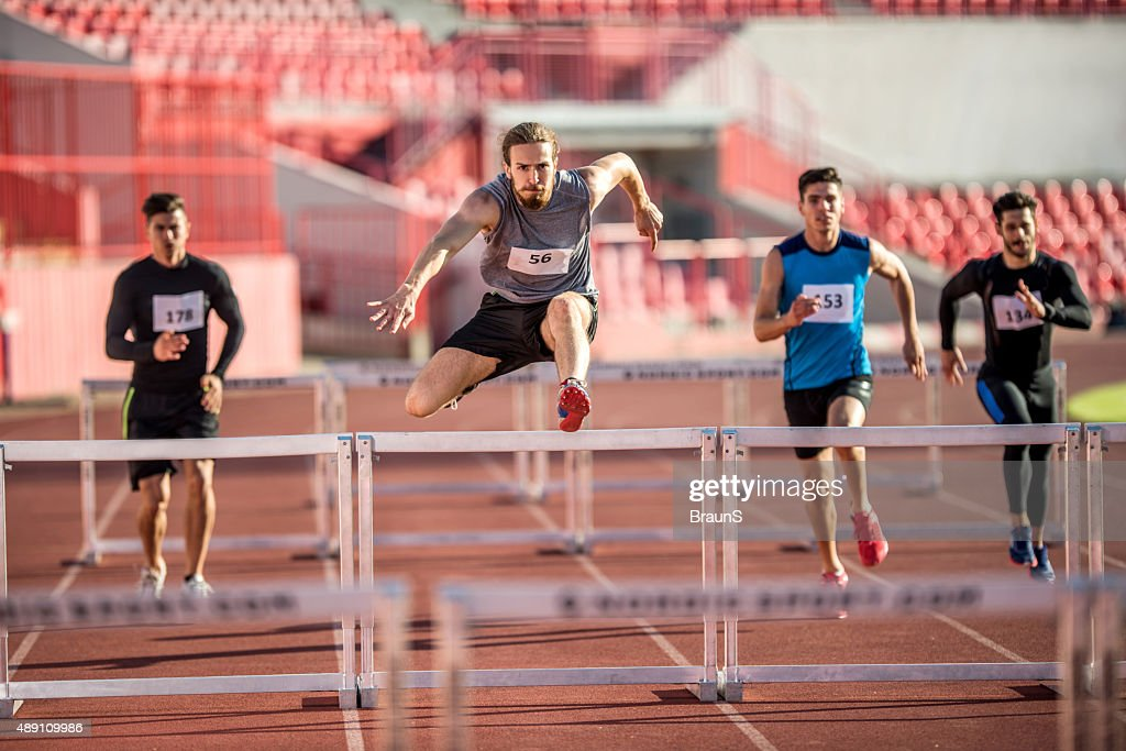 Young male athletes jumping hurdles on a sports race. : Stock Photo
