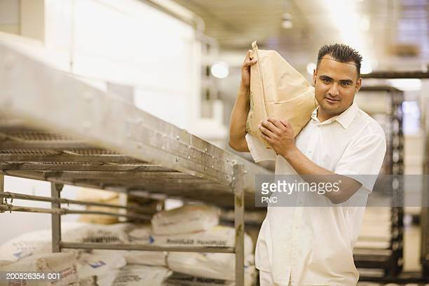 Young male baker carrying sack of flour in bakery, portrait