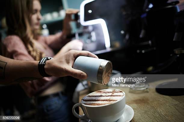 Young male barista preparing coffee in urban cafe