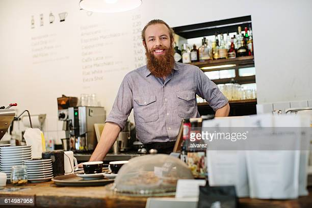 Young male barista standing at a coffee shop