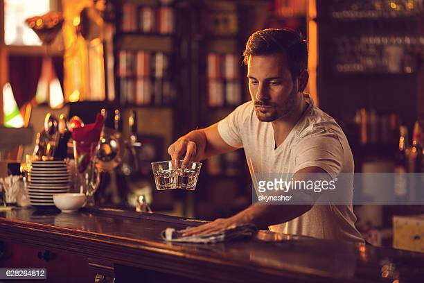 Young male bartender cleaning bar counter after work.