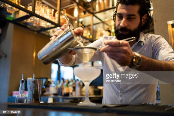 young male bartender pouring drink in glass at bar counter - cocktail party stock pictures, royalty-free photos & images