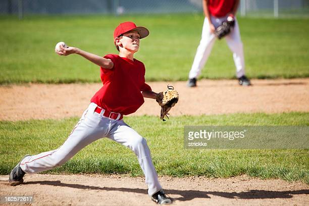 young male baseball pitcher powers through delivery - pitcher stockfoto's en -beelden