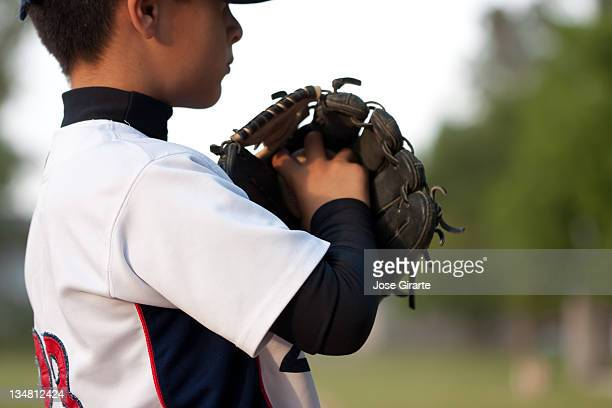 A young male baseball player holding his hand in a mitt