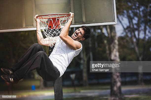Young male basketball hanging from basketball hoop