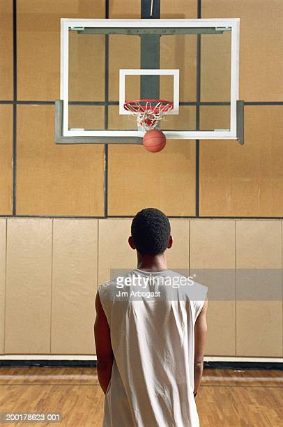 young male basketball player making a basket, rear view - shooting baskets stock photos and pictures