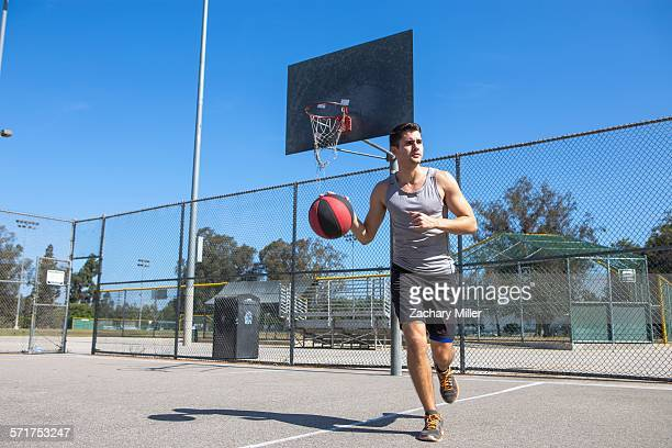 Young male basketball player running with ball on basketball court