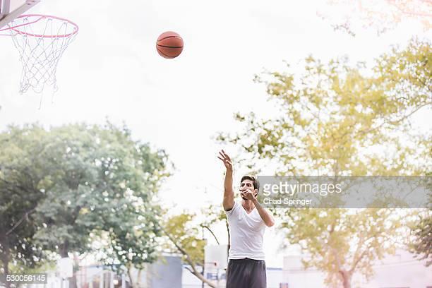 young male basketball player throwing ball towards basketball net - lanzar actividad física fotografías e imágenes de stock