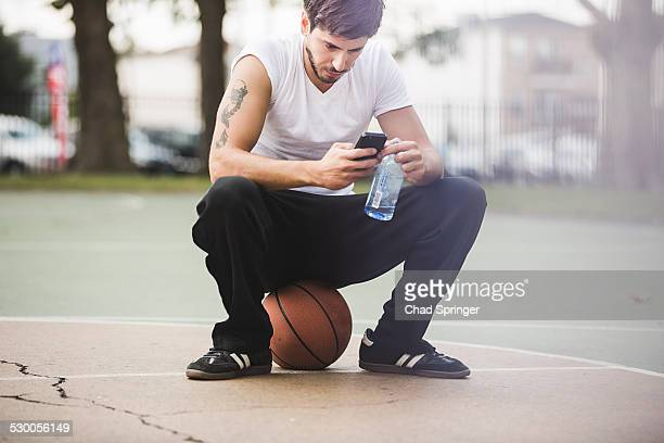 Young male basketball sitting on ball texting on smartphone