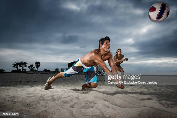 Young male beach volleyball player diving to hit ball