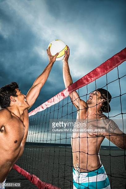 Young male beach volleyball players competing at volleyball net