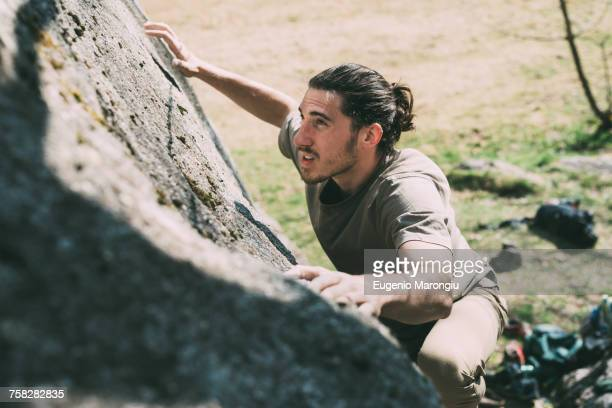 young male boulderer climbing up boulder, lombardy, italy - concentrazione foto e immagini stock
