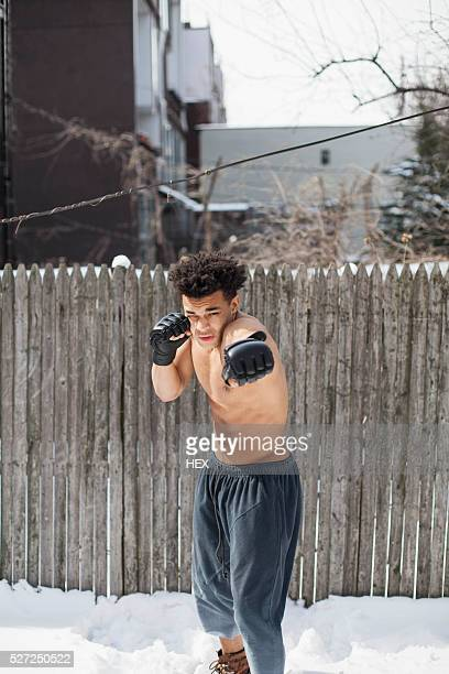 young male boxer posing in the snow - halbbekleidet stock-fotos und bilder