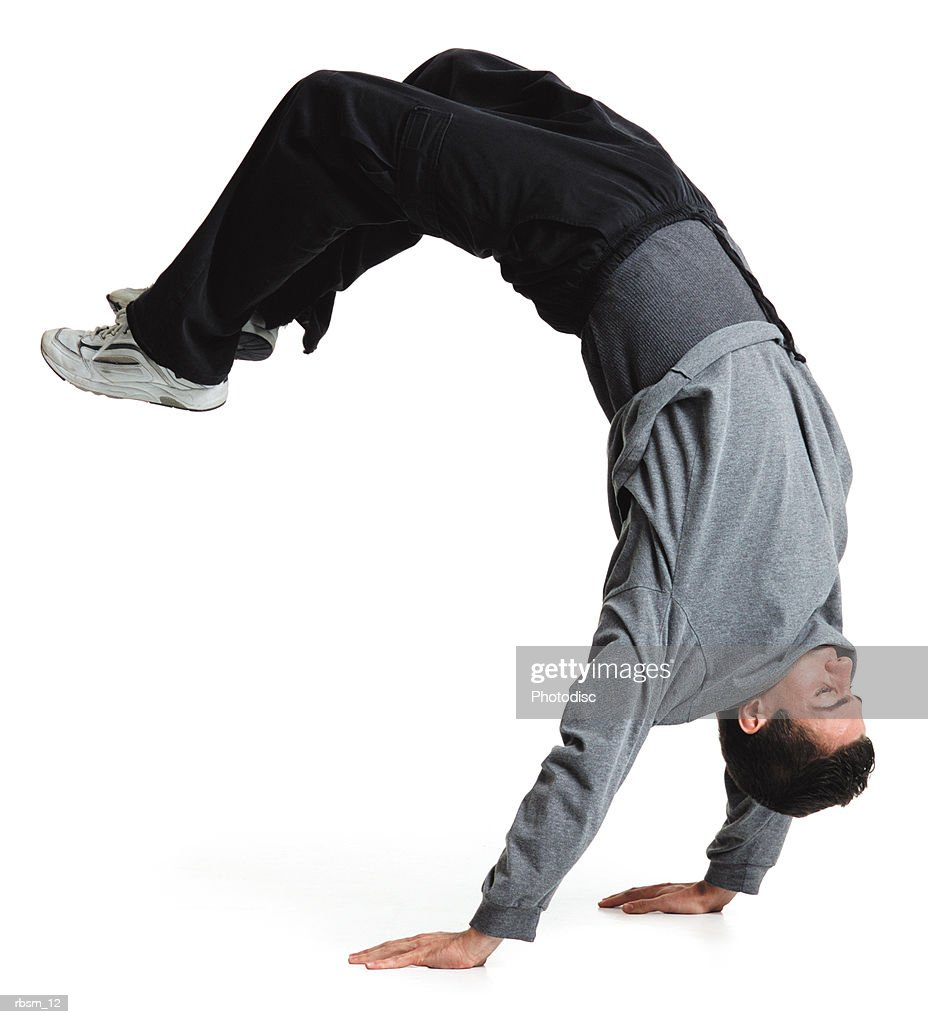 young male breakdancer black pants and grey sweatshirt flips upside down and balances on his hands : Foto de stock