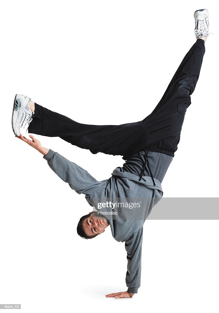 young male breakdancer black pants grey top flips upside down balances on his hand legs in the air : Foto de stock