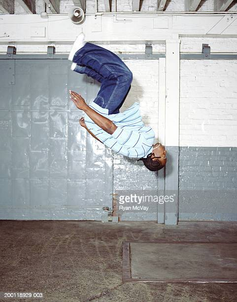 Young male breakdancer doing backflip, side view