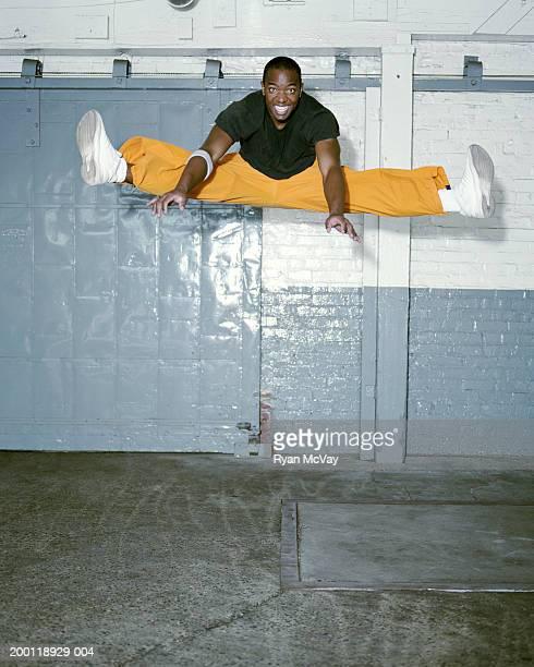 breakdancer macho joven haciendo se divide en aire, sonriendo - black pants fotografías e imágenes de stock