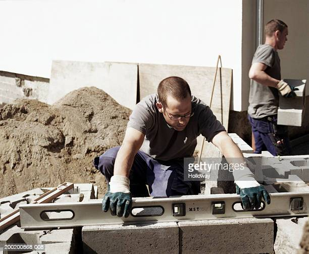 Young male builder using spirit level on concrete blocks in garden