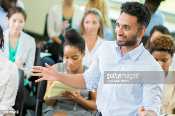 Young male business graduate student lectures undergraduate students