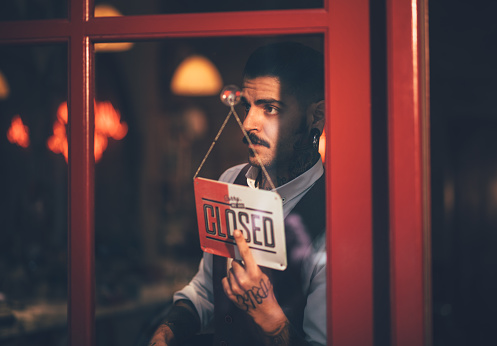 Young male business owner holding closed shop sign at window 915640268