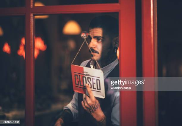 young male business owner holding closed shop sign at window - cartello chiuso foto e immagini stock