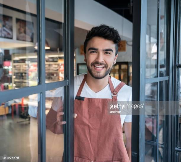 Junge männliche Unternehmer eines Lebensmittels zu speichern, öffnen die Türen Blick in die Kamera einsatzbereit
