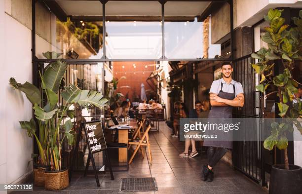 young male business owner standing outside hipster urban café - small stock pictures, royalty-free photos & images